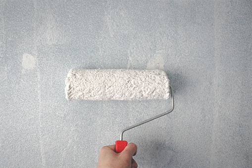 A hand painting a wall with a paint roller.